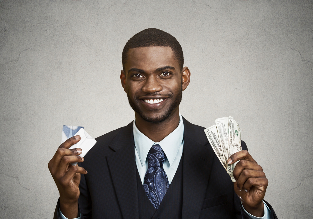 Closeup portrait happy, smiling business man company employee standing, holding dollar bills, credit card hand isolated grey black background. Banking exchange rate concept. Facial expression reaction-1