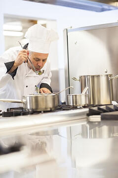 Concentrating head chef tasting food from ladle in professional kitchen