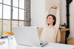 Happy relaxed young woman sitting in her kitchen with a laptop in front of her stretching her arms above her head and looking out of the window with a smile-2