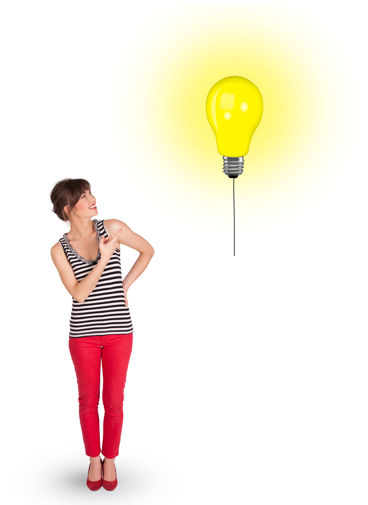 Happy young woman holding a light bulb balloon