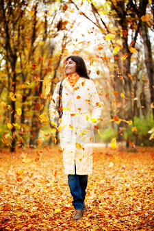 Autumn woman walking outdoors and leaves falling on her