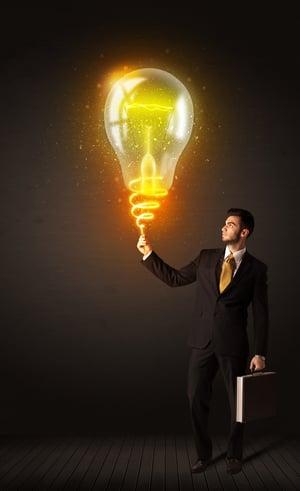 Businessman holding a shining idea bulb