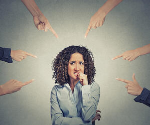 Concept of social accusation of guilty businesswoman many fingers pointing at isolated on grey office wall background. Portrait scared anxious embarrassed woman biting fingernails-1