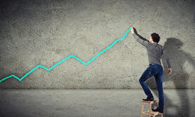 Young man drawing a financial graph on the wall